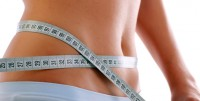 Close up of a slim waist with measuring tape.